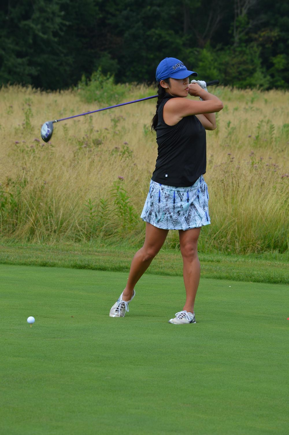 An alumna golfing at the Meadows Golf Course.